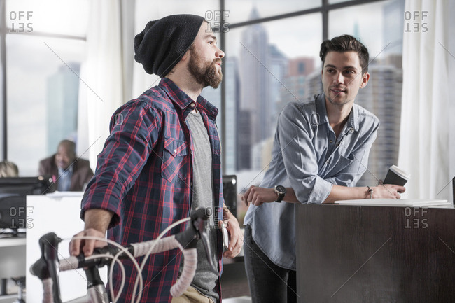 Casual man with bike in modern office