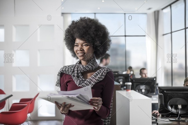 Smiling woman holding documents in office