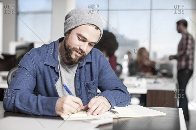 Man writing down notes at desk in office