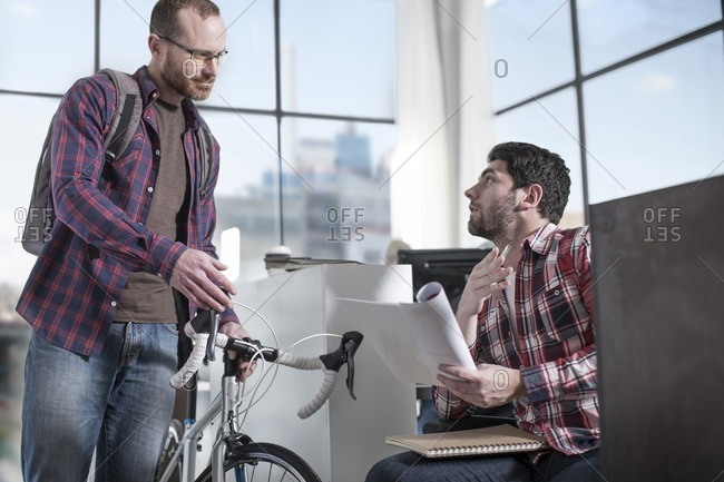 Casual man with bike in modern office talking to colleague