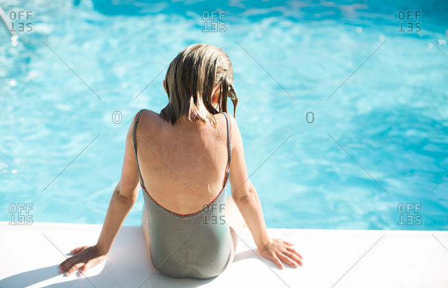 Rear view of girl sitting at the edge of swimming pool