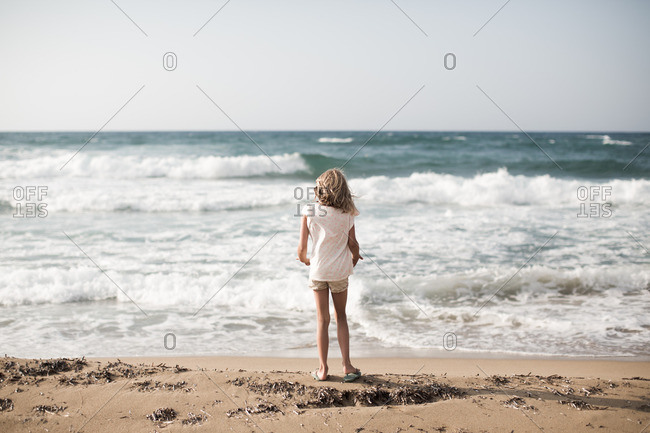 Rear view of little girl watching the waves at beach during summer vacation.