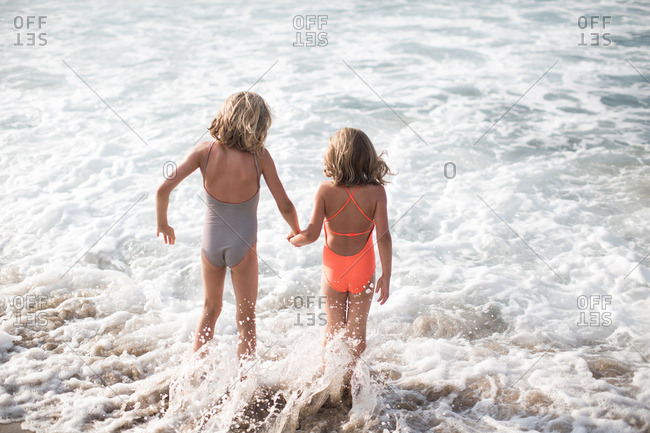 Rear view of little girls at the beach standing in sea waves