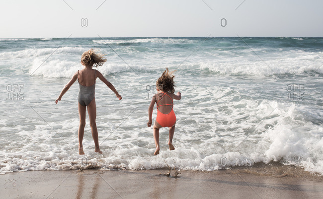 Rear view of two little sisters in swimsuit jumping on the beach.