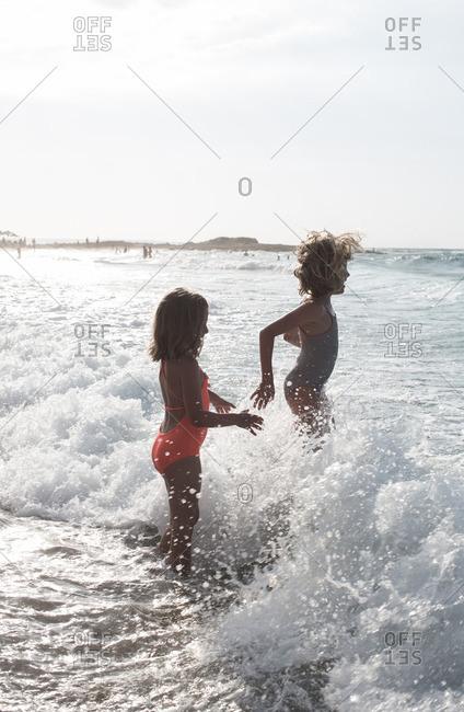Girls having fun in splashing waves at the beach.