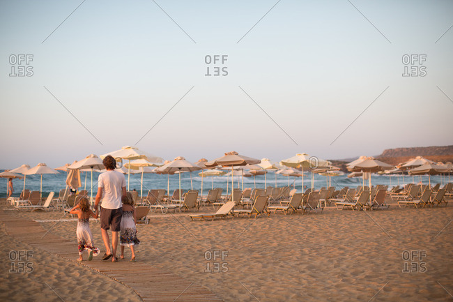 Rear view of father with daughters walking on boardwalk at the beach