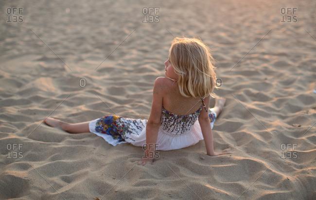 Little girl lying on the sand at beach