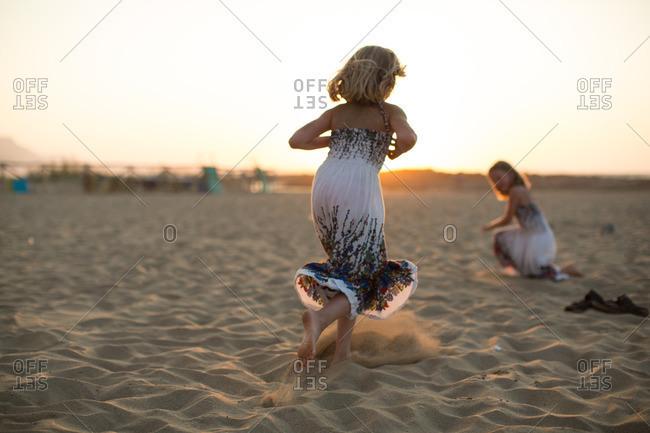 Little girls running on sand during sunset