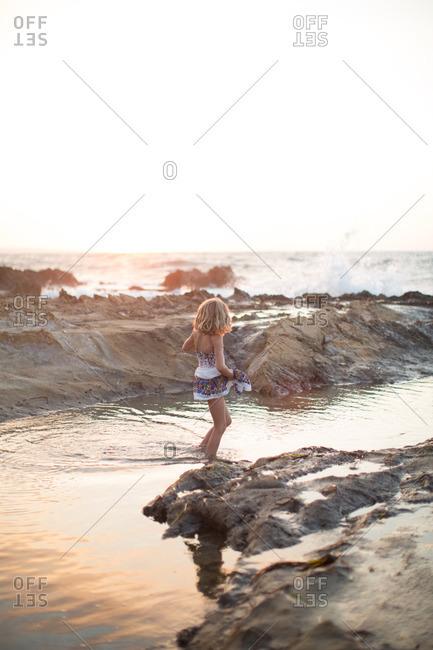 Little girl standing in sea water amidst rocky coastline