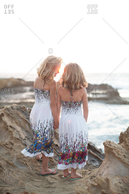 Back view of little girls standing at rocky coastline during summer vacation