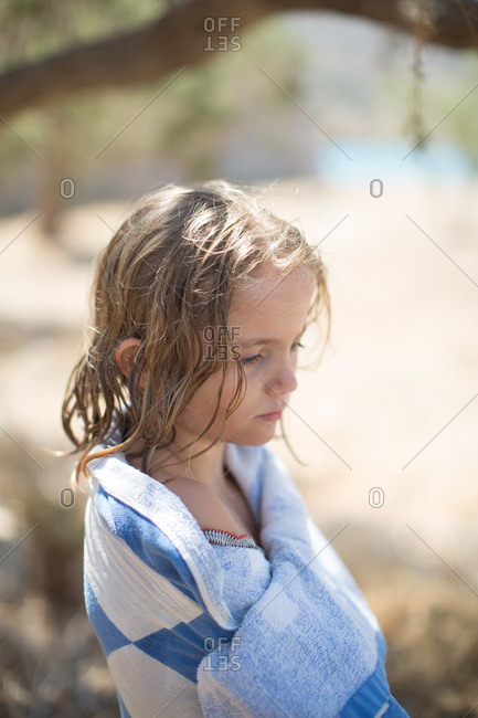Sad little girl wrapped in a towel at beach