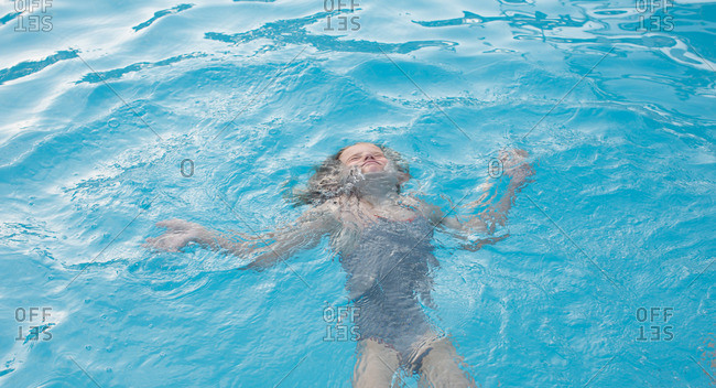 Little girl swimming at pool water surface