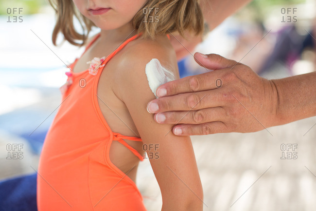Father applying sunblock cream on daughter's hand
