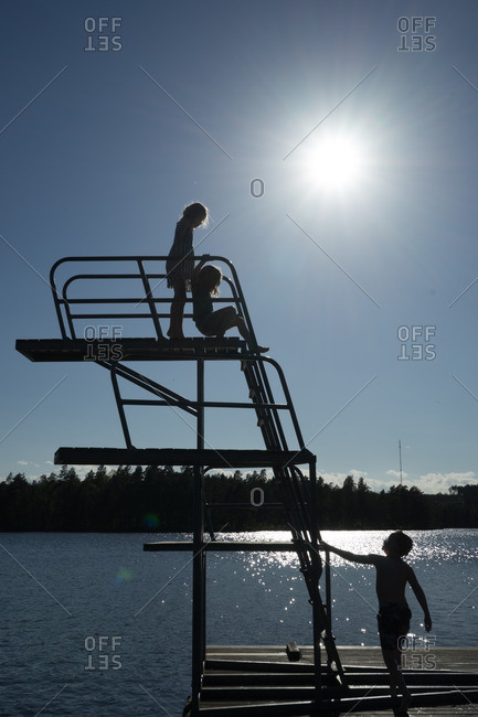 Silhouette of children on diving board