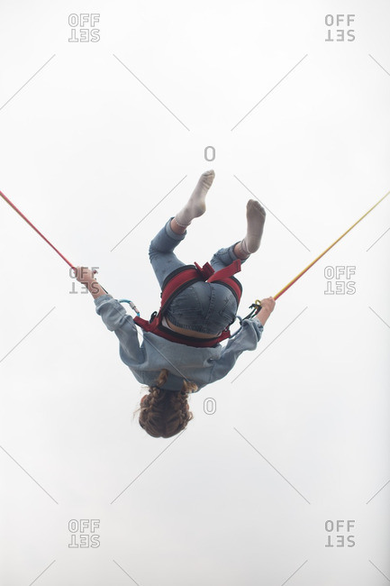 Low angle view of girl bouncing on bungee trampoline