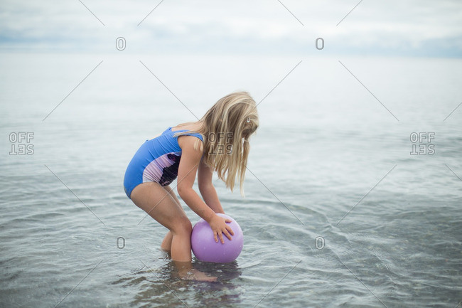 Girl picking up ball in sea
