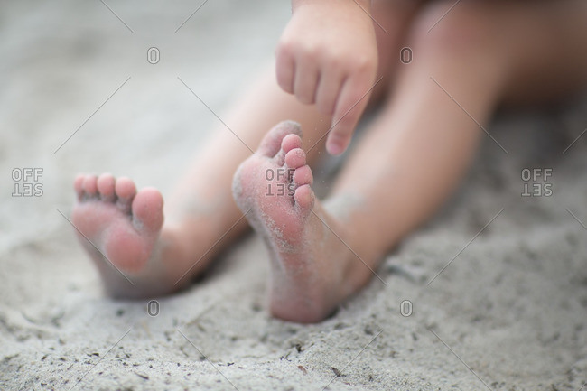 Close up of girl's legs on sand at beach