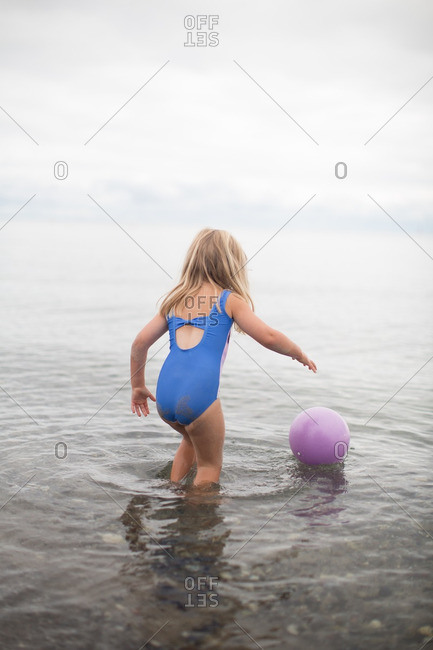 Girl in swimsuit with ball floating on sea water surface