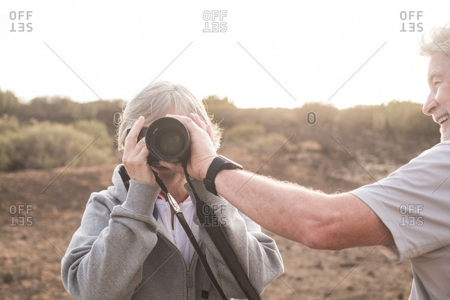 Tenerife, Canary Islands, Spain - February 3, 2017: Senior woman looking through camera while husband turns lens to zoom