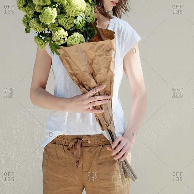 Woman with bouquet of flowers wrapped in brown paper