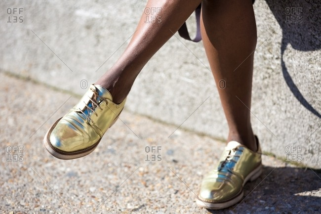 Woman with legs crossed wearing gold shoes