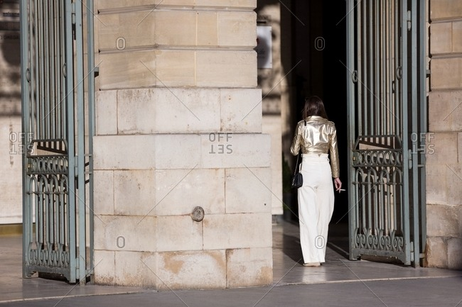 Back view of woman in white pants and gold leather jacket smoking a cigarette outside building