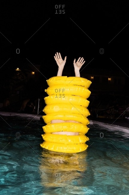 Person in swimming pool inside stack of yellow tubes