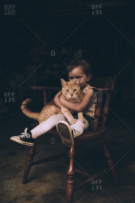 Little girl sitting in a wooden chair holding her pet cat