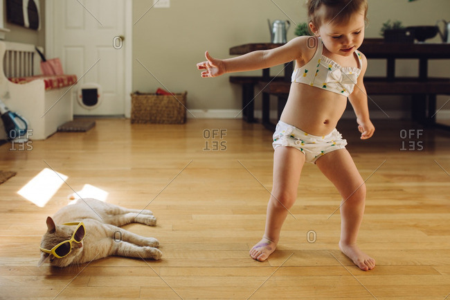 Toddler girl in a bathing suit playing with her pet cat