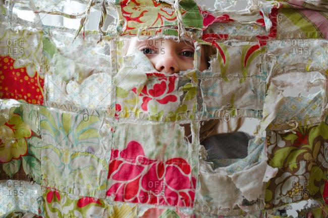 Girl looking through tattered blanket