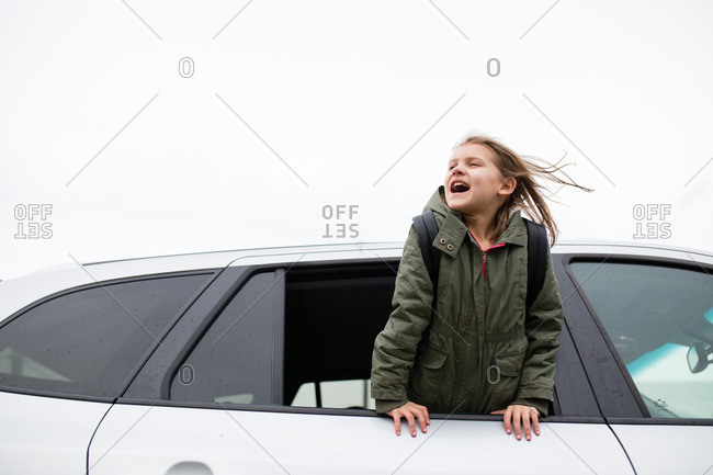 Girl yelling out car window in wind