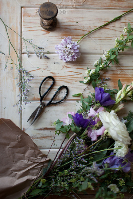Flower arrangement being prepared on a wooden table