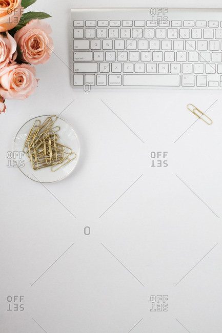 Computer keyboard beside roses and a paperclips