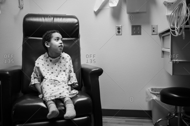 Girl in hospital gown waiting in char