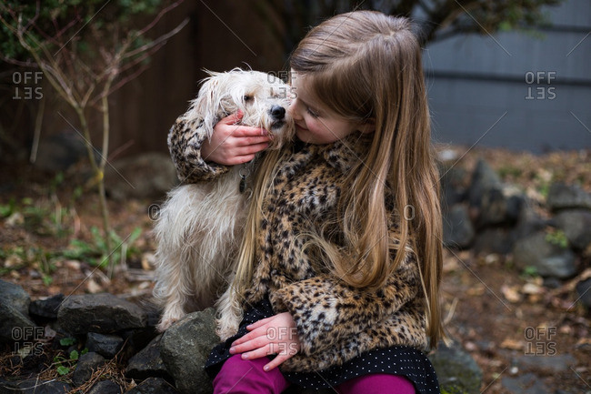 Girl snuggling a dog outdoors
