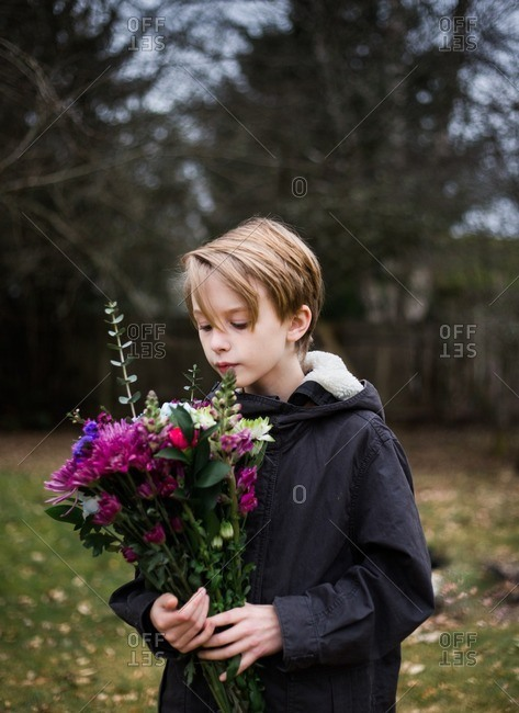 Boy looking at flower bouquet outside
