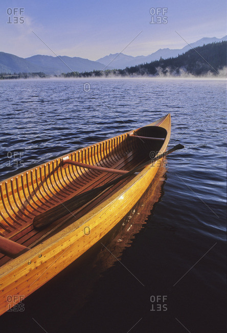 A cedar canoe waits for paddlers as the mist rises on Alta Lake in the autumn, Whistler, BC Canada