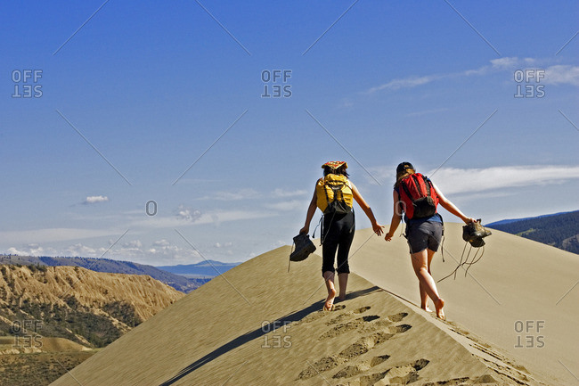 Kids playing on sand dunes in Farwell Canyon Area, British Columbia, Canada