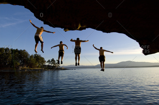 Four people jump from the cliffs of the Malaspina Galleries into the Pacific Ocean, Gabriola Island, BC Canada