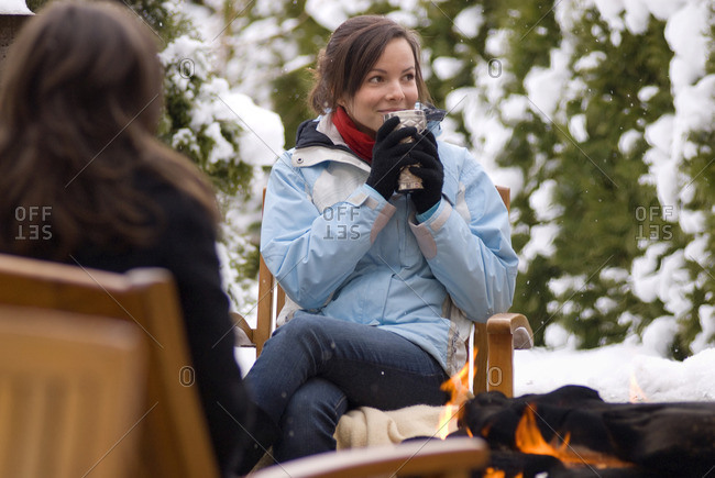 Whistler, British Columbia, Canada - December 30, 2008: A teenage girl enjoys a hot drink in the winter snow by an outdoor fire