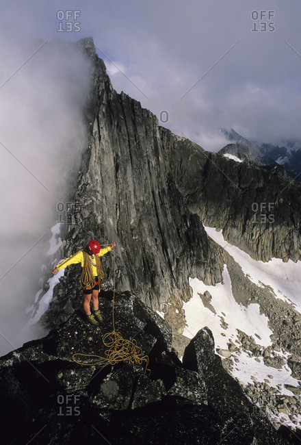 Senja Palonen coils a rope on the summit of North Nesakwatch Spire after climbing the North Ridge route, Chilliwack Valley, British Columbia, Canada