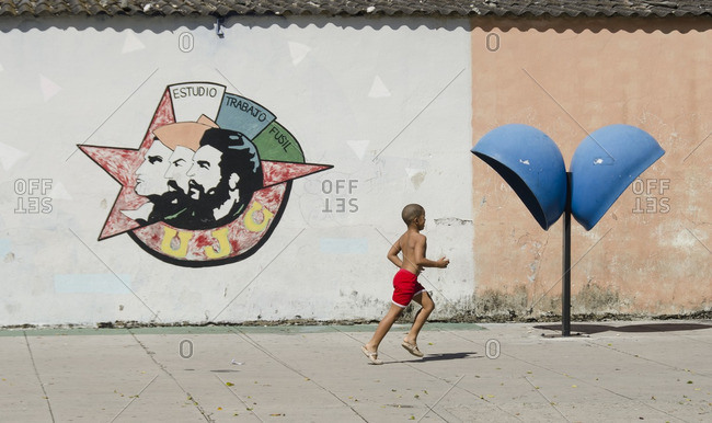Havana, Cuba - October 10, 2013: Boy running and mural exhorting study, work and the revolution