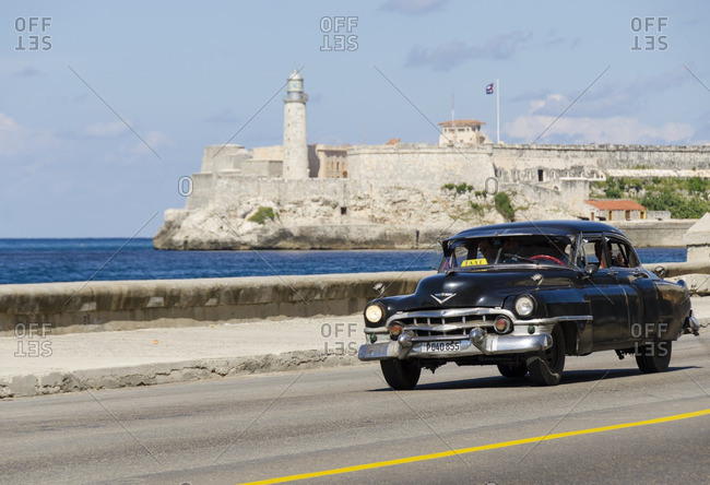 Havana, Cuba - October 13, 2013: Vintage american cars along the Malecon, behind is Morro Castle, a picturesque fortress guarding the entrance to Havana bay