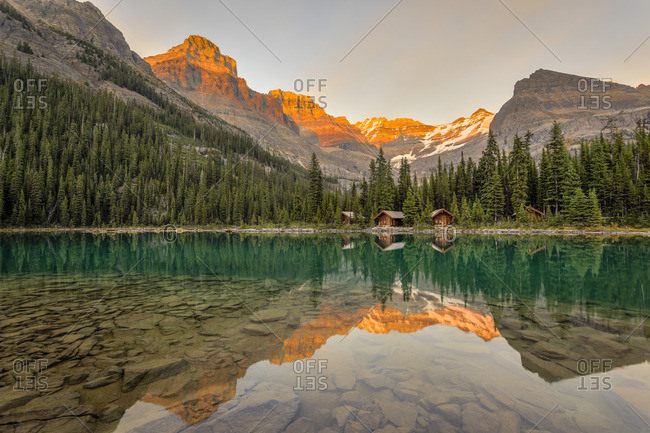 Lake O\'Hara Lodge guest cabins and peaks are reflected in the calm lake at sunset Lake O\'Hara, Yoho National Park, British Columbia