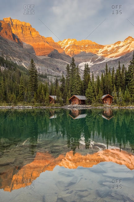 Lake O'Hara Lodge guest cabins are reflected in the calm lake at sunset Lake O'Hara, Yoho National Park, British Columbia Canada