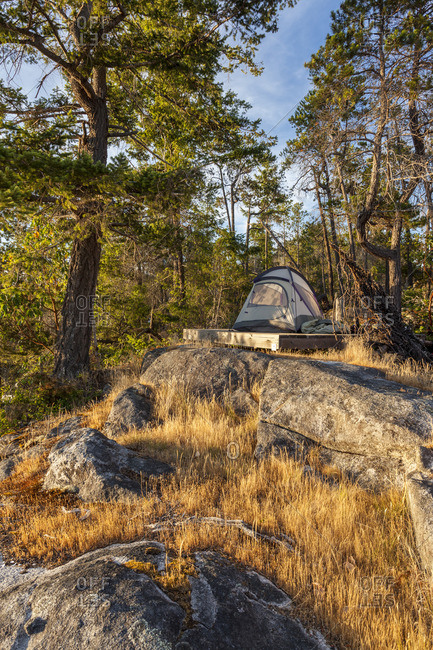 The sun sets on a kayaker's tent on West Curme Island in Desolation Sound Marine Park, British Columbia, Canada