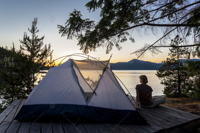 A camper relaxes on a platform next to her tent at dusk West Curme Island, Desolation Sound Marine Park, British Columbia, Canada Model Released