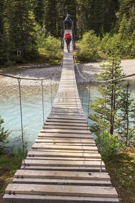 Two back packers cross a suspension bridge over a river in Kootenay National Park, British Columbia, Canada Model Released