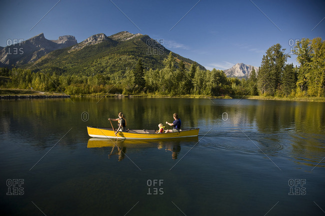 Elk Valley, British Columbia, Maiden Lake, Fernie - September 17, 2008: Young family canoeing on Maiden Lake with Mount Fernie and Mount Hosmer in background