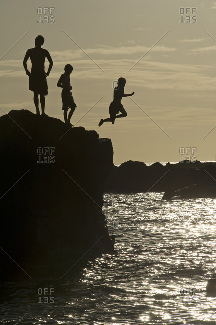Youth jumping from the rock into the sea at sunset